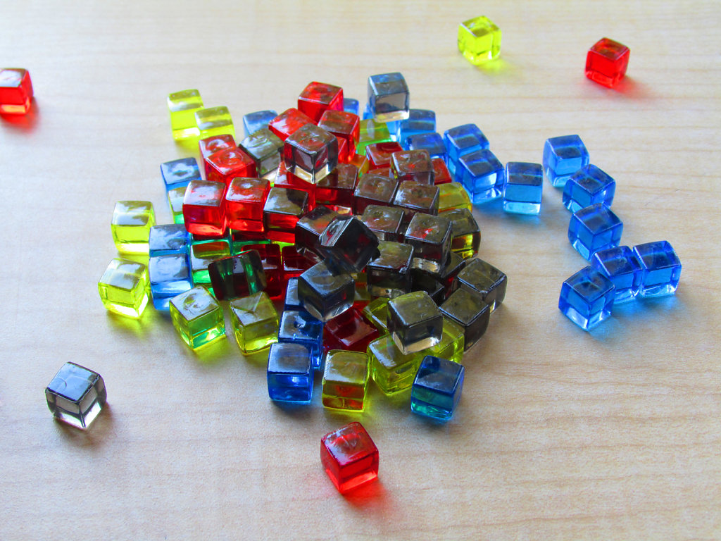Colored translucent game cubes scattered on a table