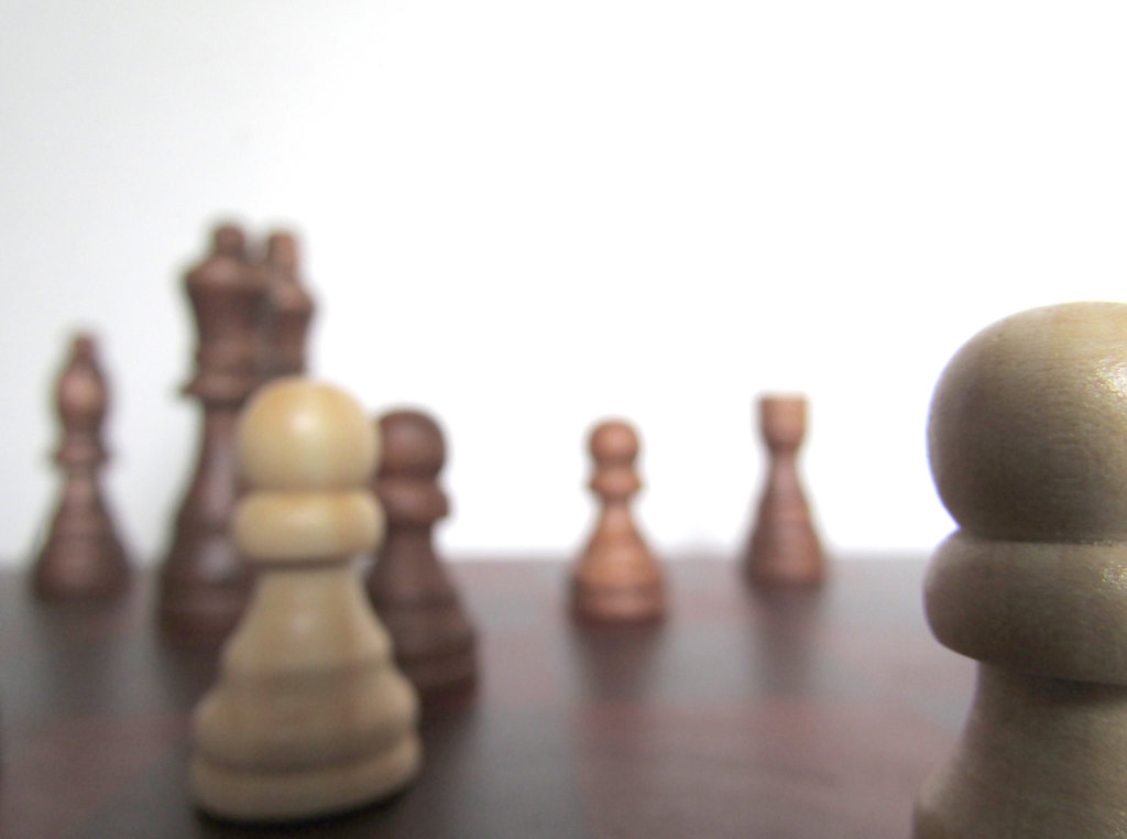 Wooden chess pieces with one in focus