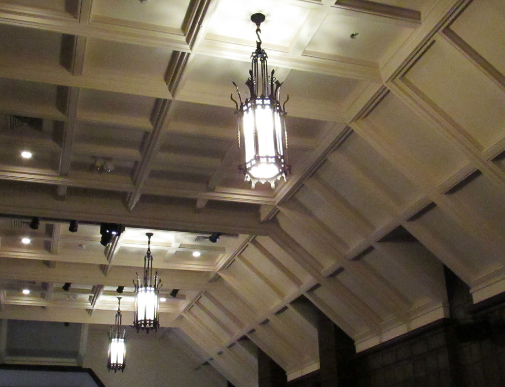 Three cast iron ceiling lights hanging from a decorated ceiling