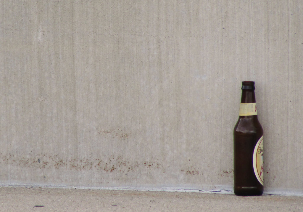 beer bottle against a concrete wall