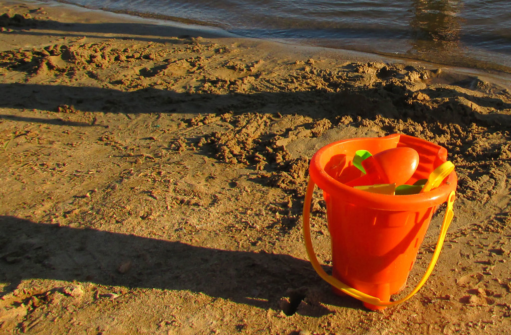 Kids orange sand bucket on beach